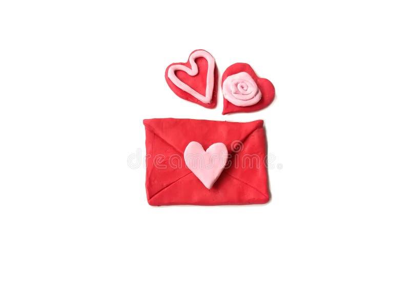 Roter Umschlag Plasticine, roter Herzlehm der netten Paare, reizender Geschenkteig, weißer Hintergrund stockfotos