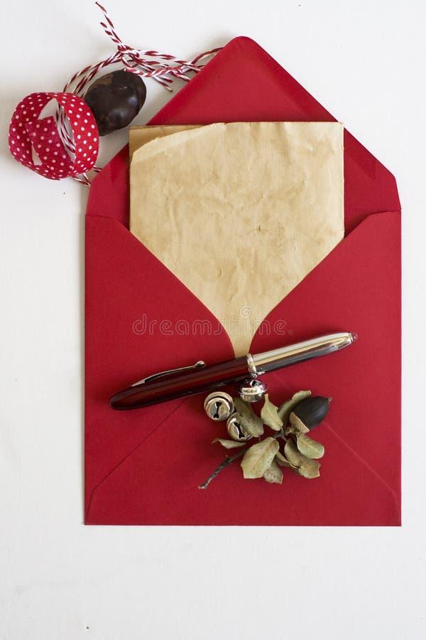 Roter Umschlag, Weihnachtsbrief, weißer Hintergrund und Verzierungen stockfotografie