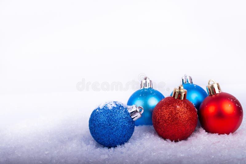 Roter und blauer Ball der Weihnachtsdekoration in einem Baum mit Lametta und pinecone im Schnee stockfotografie