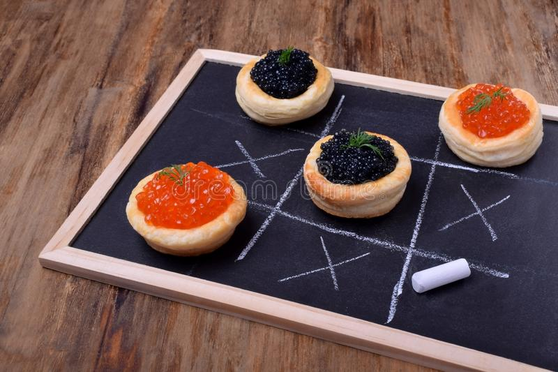 Roter und schwarzer Kaviar in den Tartlets auf einer Tafel lizenzfreie stockfotografie