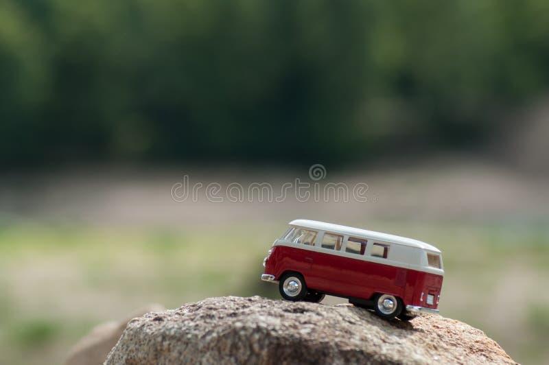 roter und weißer Miniaturpackwagen auf dem Felsen im Berg auf Waldhintergrund lizenzfreie stockfotos