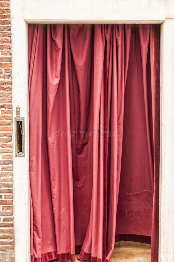 Roter Vorhang, der in einem Eingang hängt stockfotos