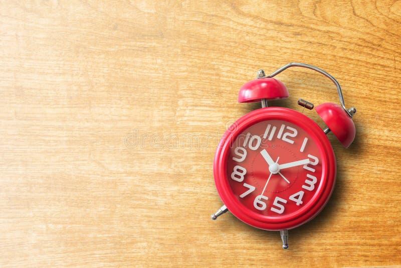 Roter Wecker auf altem braunem hölzernem Plankenhintergrund lizenzfreies stockfoto