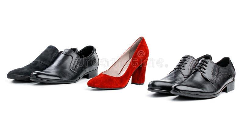 Roter weiblicher Schuh zwischen schwarzen männlichen Schuhen in der Reichweite stockfotografie