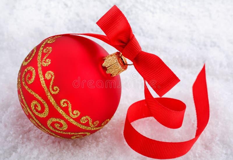 Roter Weihnachtsball mit Verzierung auf Schnee stockfotografie