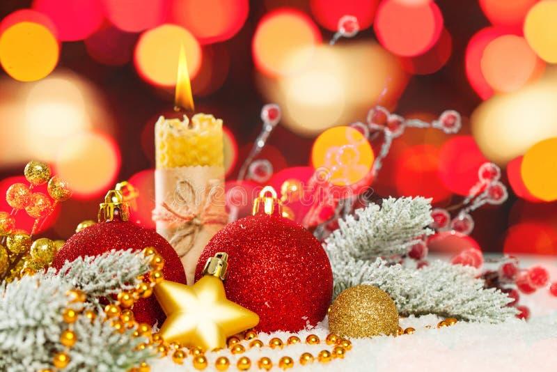 Roter Weihnachtshintergrund mit abstraktem bokeh Licht, roter Flitter, Kerze und grüner Tannenzweig auf Schnee Frohe Weihnacht-Au stockfoto