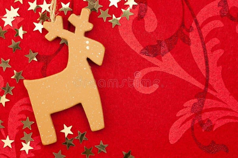 Roter Weihnachtshintergrund mit handgemachtem Ren, goldene Sterne lizenzfreie stockfotos