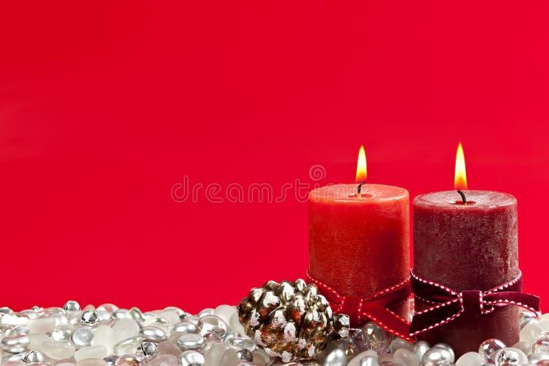 Roter Weihnachtshintergrund mit Kerzen stockbild