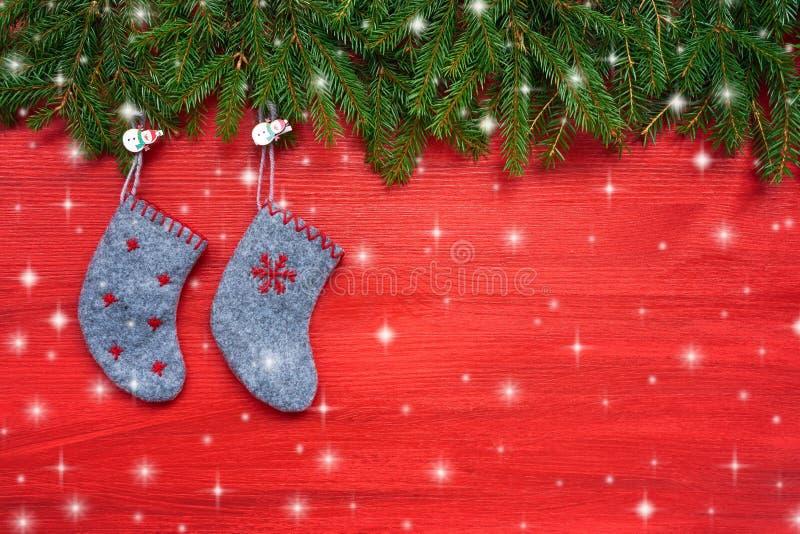Roter Weihnachtshintergrund Weihnachtstannenbaum und Weihnachtssocken auf rotem hölzernem Hintergrund Kopieren Sie Platz lizenzfreie stockfotografie