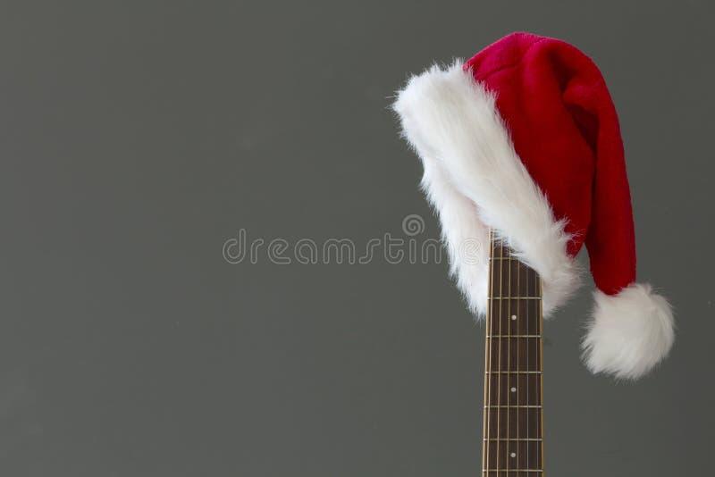 Roter Weihnachtshut auf Gitarre, Lied der frohen Weihnachten lizenzfreies stockfoto