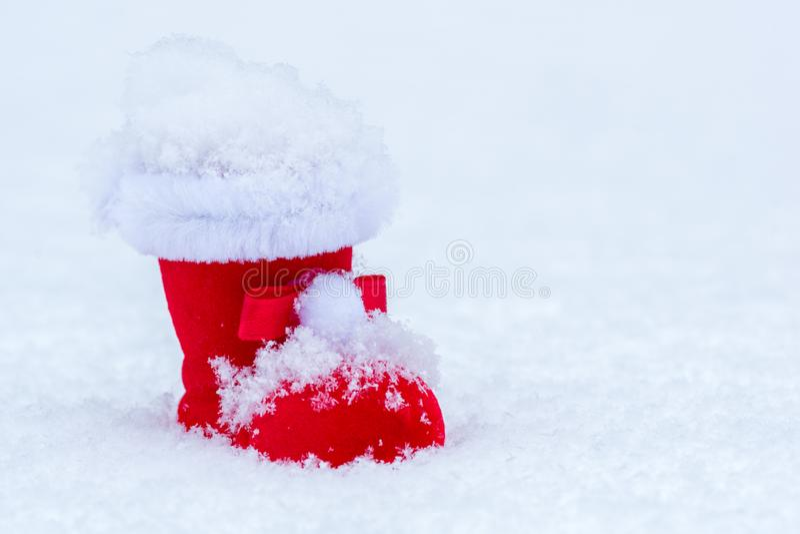 Roter Weihnachtsstiefel im Schnee mit Schneeflocke und weißem Hintergrund stockbilder