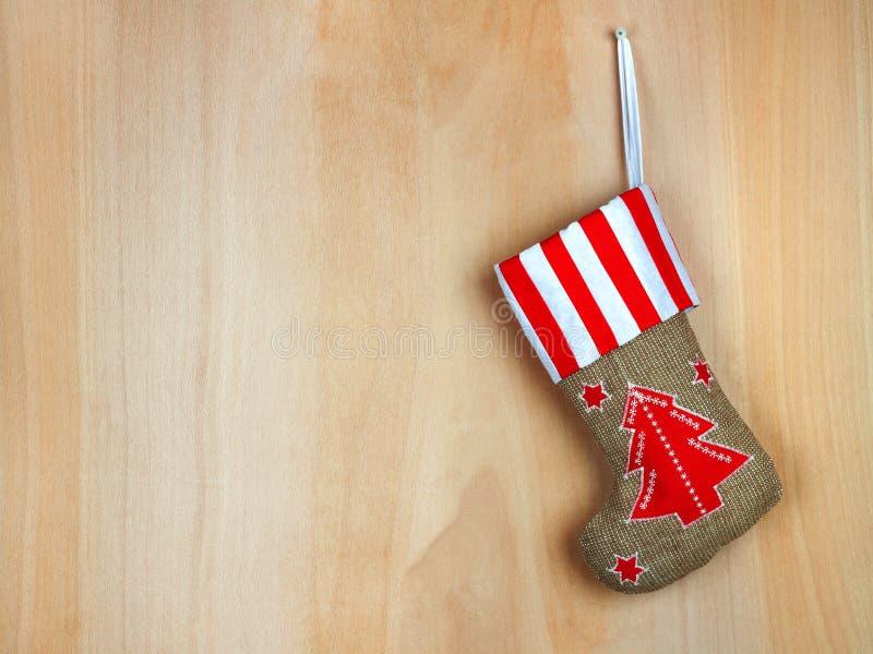 Roter Weihnachtsstiefel mit Geschenken auf hölzerner Wand lizenzfreies stockfoto
