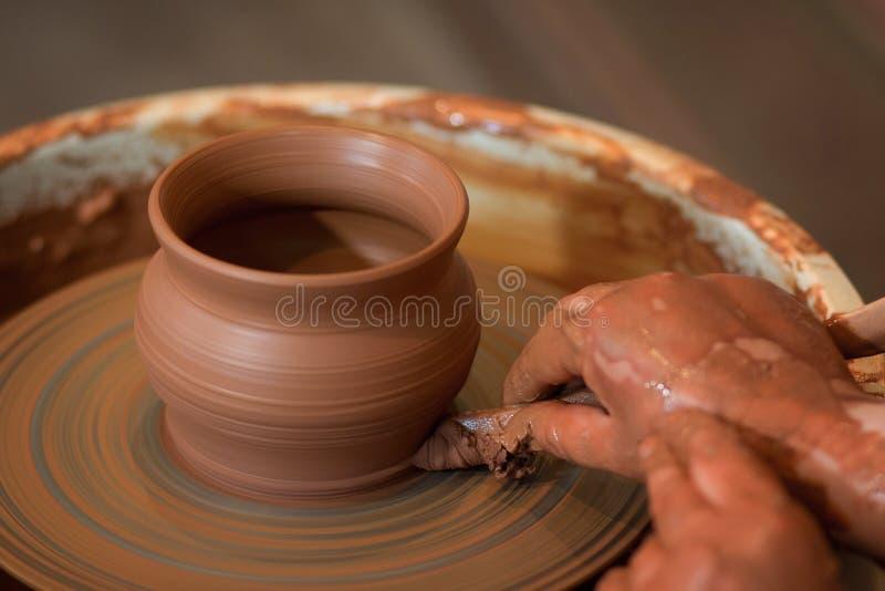 Roterande keramiker` s rullar och leraware på den som tas från över Hugger hans händer med en lerakopp på keramikers hjul arkivbild