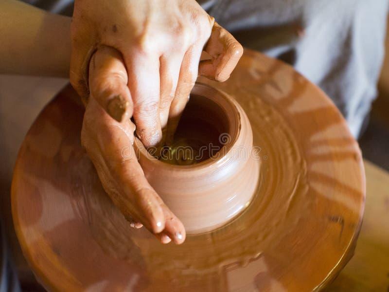 Roterande keramiker` s rullar och leraware på den vasen: taget från över Händer i lera Krukmakeri: den manliga ceramisten skapar  arkivbilder