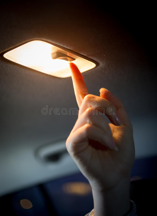 Roterande ljus för kvinna på i bilsalong royaltyfri bild