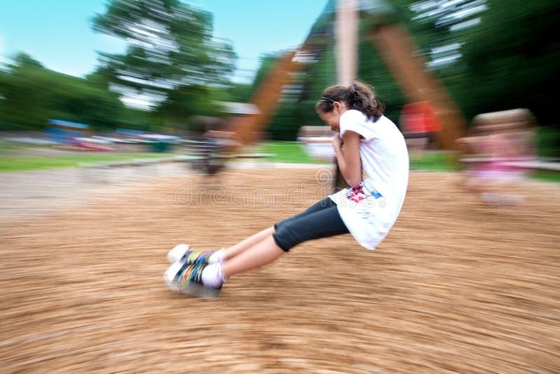 roterande swing för flickalekplats royaltyfria foton