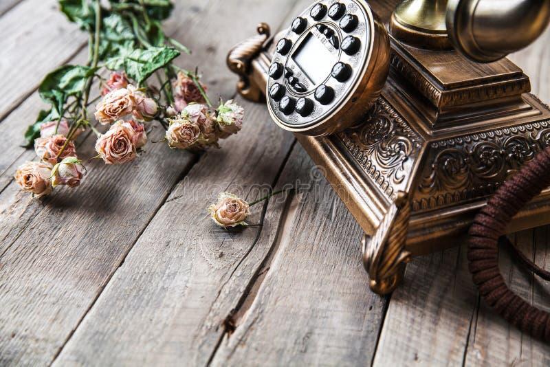 Roterande telefon för gammal tappningsvart och en bukett av rosor på träbakgrund arkivbilder