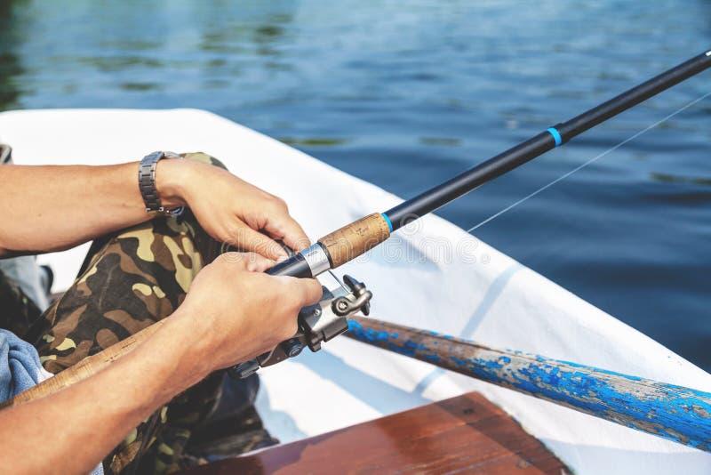 Roteras den hållande metspöet för handfiskaren och rullhandtaget royaltyfri bild