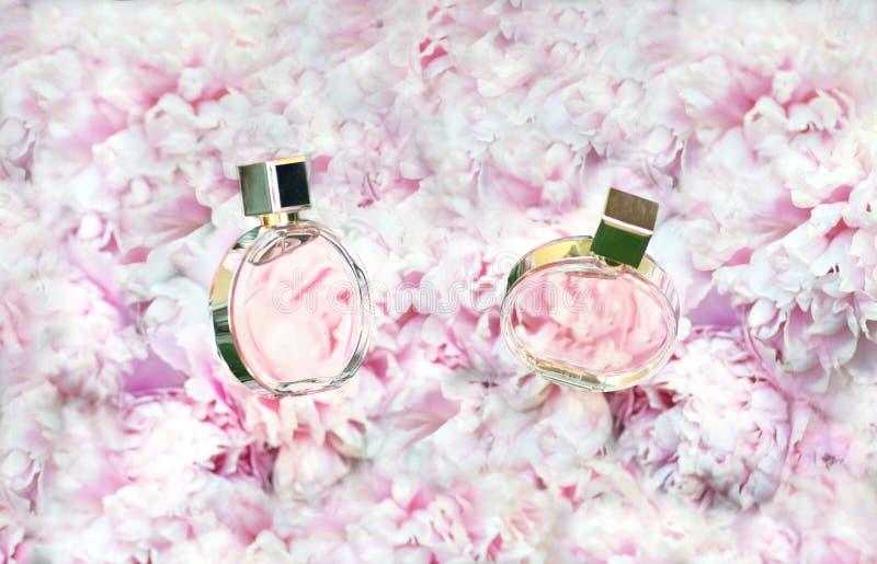 Roterende Parfumflessen op de roze achtergrond van bloemenpioenen met exemplaarruimte Parfumerie, schoonheidsmiddelen, vrouwelijk stock afbeeldingen