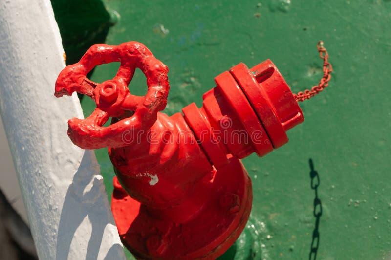 Rotes abgedroschenes Hydrantventil auf einer Fähre stockfotos