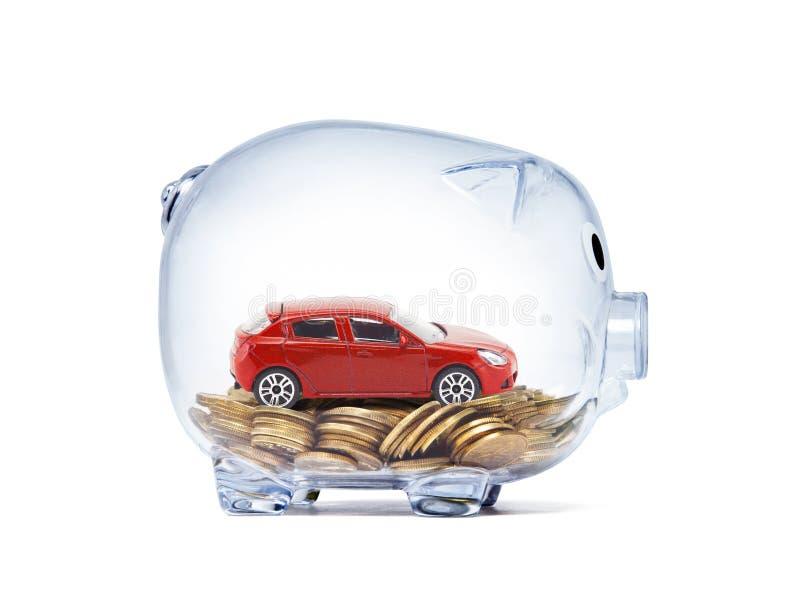 Rotes Auto auf Geld innerhalb des transparenten Sparschweins stockfotos