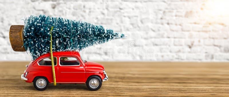 Rotes Auto, das einen Weihnachtsbaum transportiert lizenzfreie stockfotos