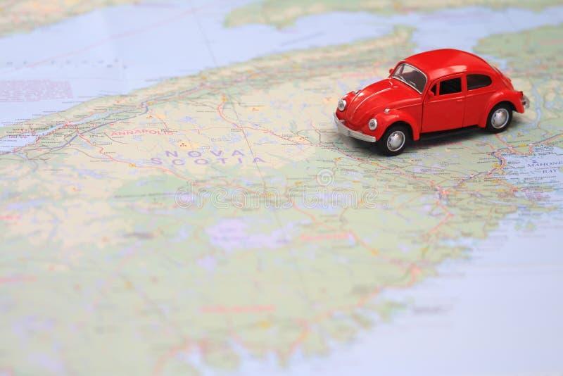 Rotes Autominiaturc$fahren auf eine Karte von Nova Scotia Kanada lizenzfreies stockfoto