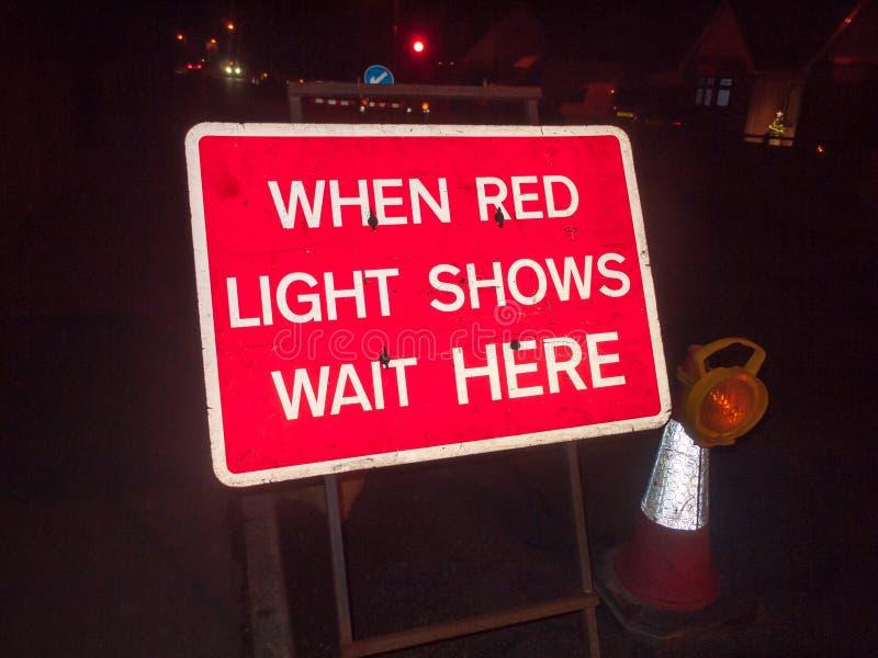 rotes Bauzeichen an der Nachtstraße, wenn Shows des roten Lichtes ihn warten lizenzfreie stockfotos