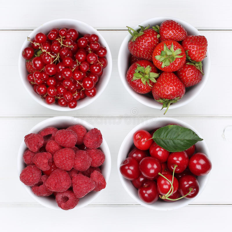 Rotes Beerenobst in den Schüsseln mit Erdbeeren, Himbeeren und che stockbild