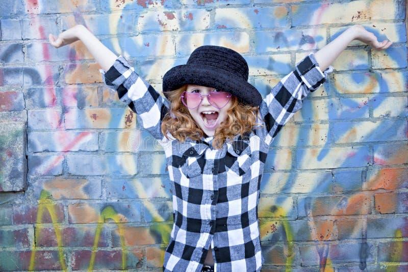 Rotes behaartes kleines Mädchen vor Backsteinmauer lizenzfreies stockfoto
