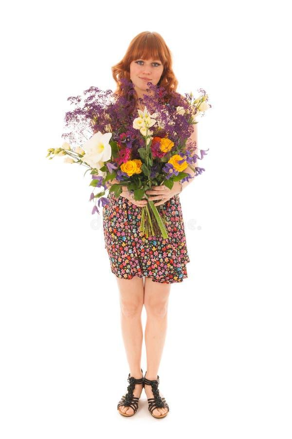 Rotes behaartes Mädchen, das mit den Blumenstraußblumen lokalisiert über Whit steht lizenzfreie stockfotos
