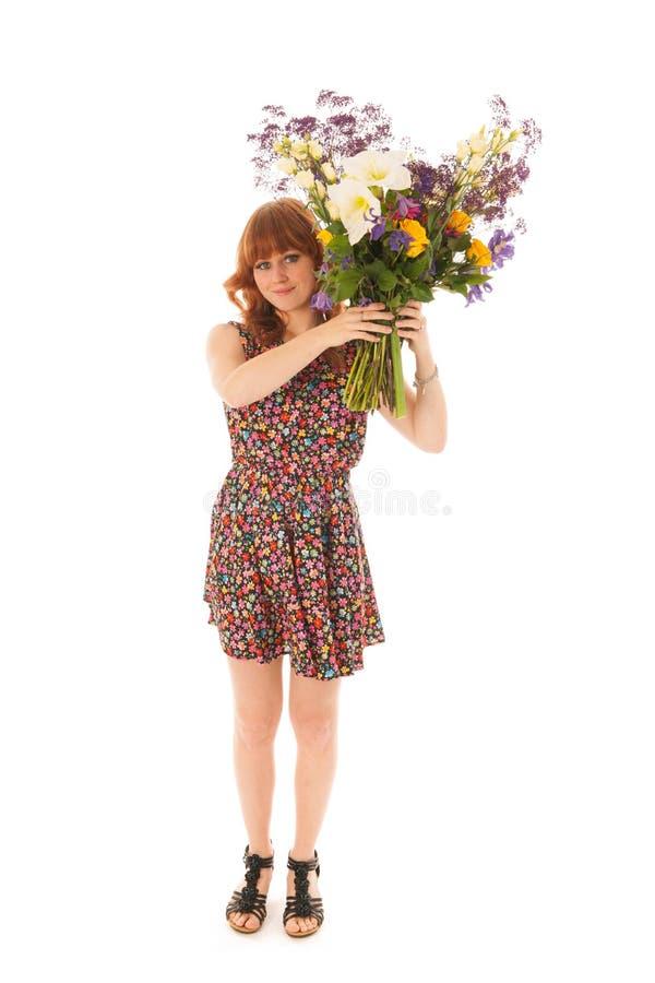 Rotes behaartes Mädchen, das mit den Blumenstraußblumen lokalisiert über Whit steht stockfoto