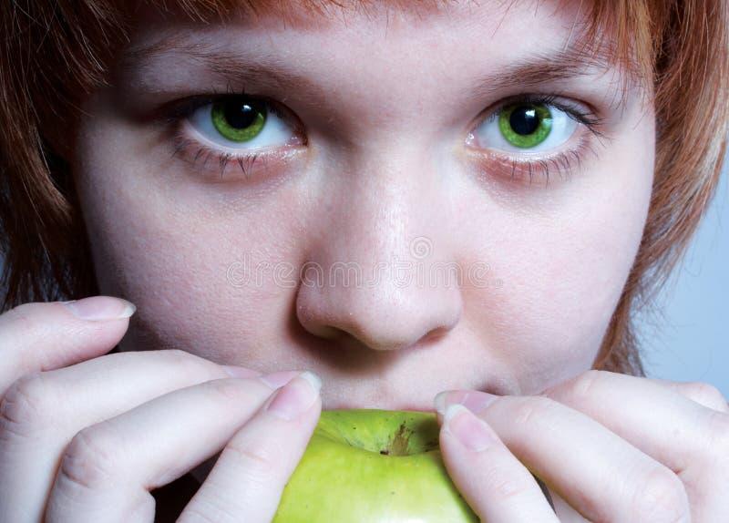 Rotes behaartes Mädchen mit grünem Apfel lizenzfreie stockbilder
