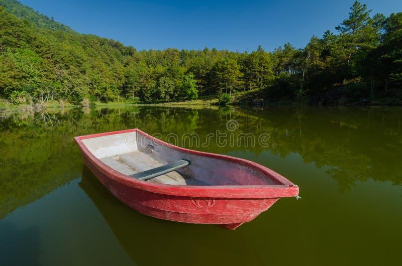 Rotes Boot im See und in der Reflexion stockfotografie