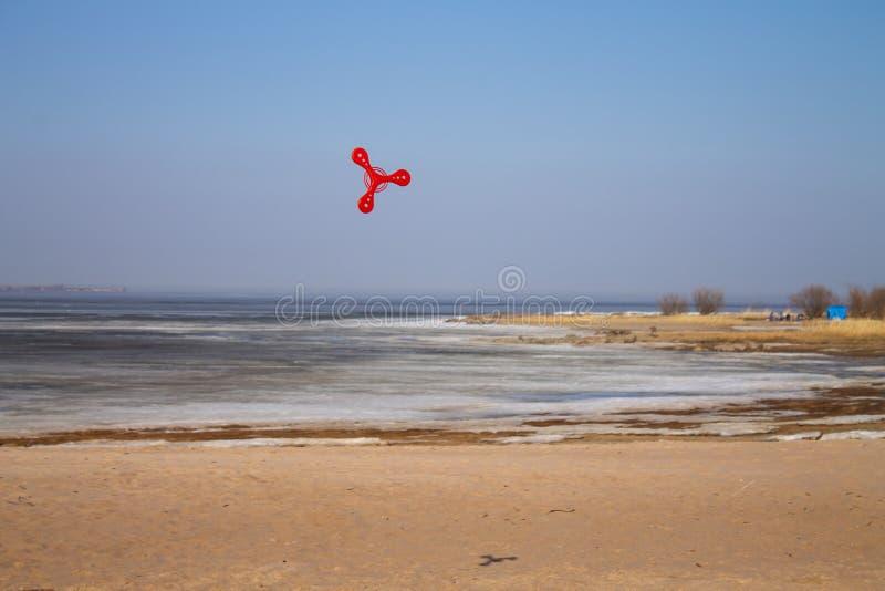 Rotes Bumerangfliegen des Spielzeugs auf Hintergrund des blauen Himmels lizenzfreies stockfoto