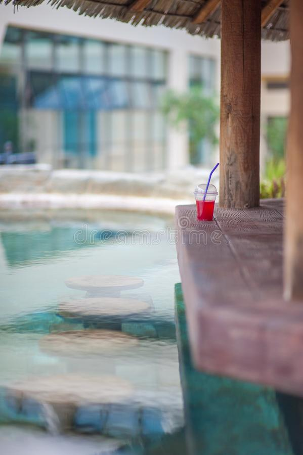 Rotes Cocktail an der Poolbar Stühle im Wasser lizenzfreie stockfotos