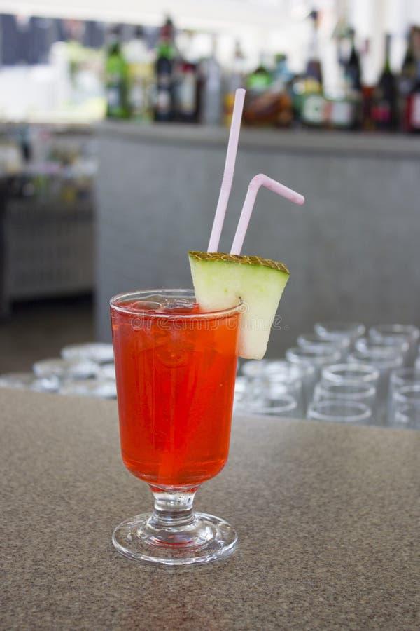 Rotes Cocktail mit einer Scheibe der Melone auf der Bar stockbild