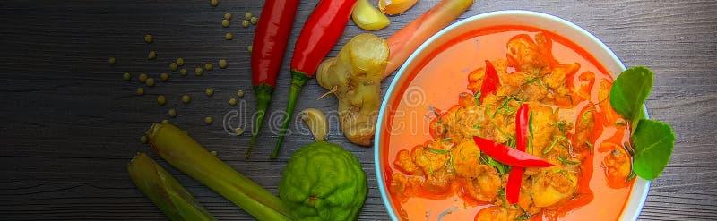 Rotes Curryhuhn, thailändisches würziges Lebensmittel und frische Krautbestandteile auf hölzerner Draufsicht/Stillleben, selektiv lizenzfreies stockbild