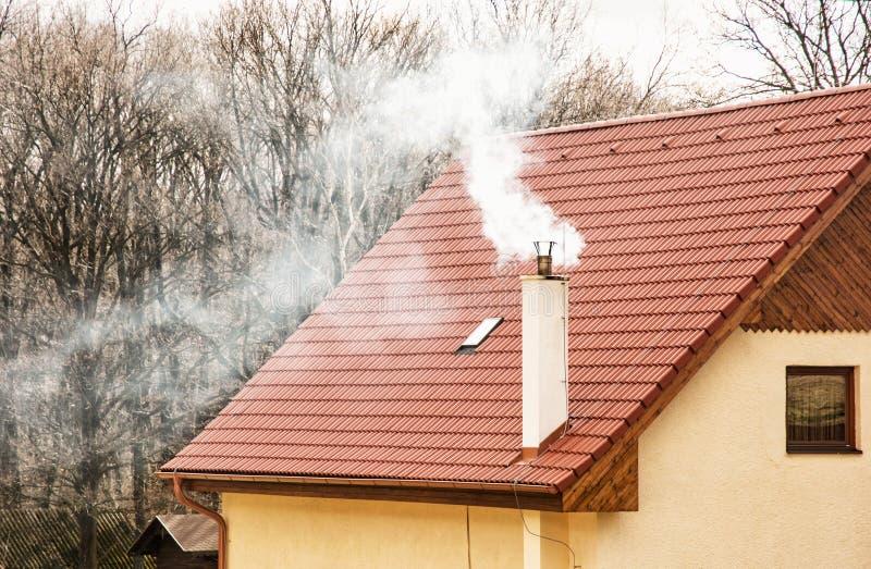 Rotes Dach und rauchender Kamin stockfoto