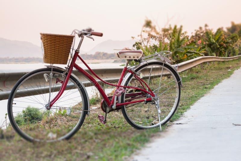 Rotes Fahrrad der Weinlese neben Flussstraße lizenzfreie stockbilder