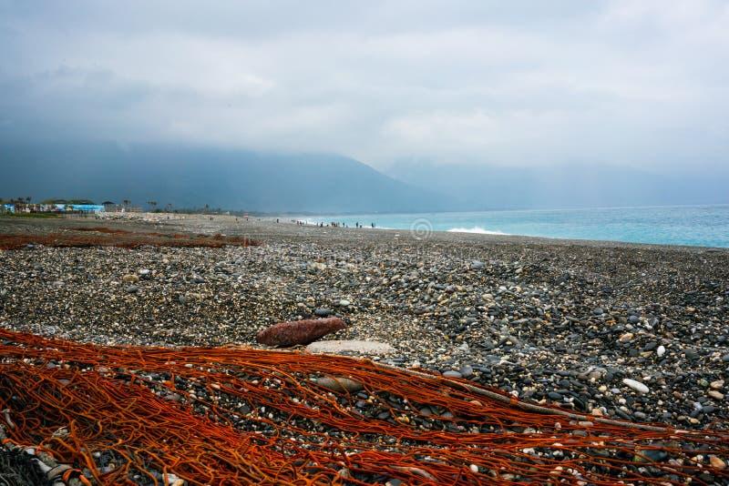 Rotes Fischernetz auf Schindelstrand mit Pazifischem Ozean und Berg lizenzfreies stockbild