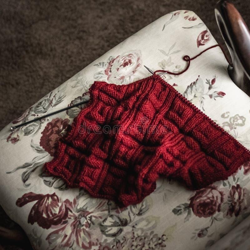 Rotes Garn-strickendes Projekt, das in einem Stuhl stillsteht stockbilder