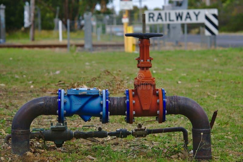 Rotes Gasrohr mit Ventil auf grünem Gras nahe Eisenbahn stockfoto