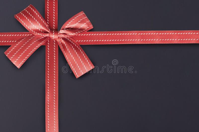 Rotes Geschenkband auf einem strukturierten Muster der Tafel im Hintergrund lizenzfreies stockfoto