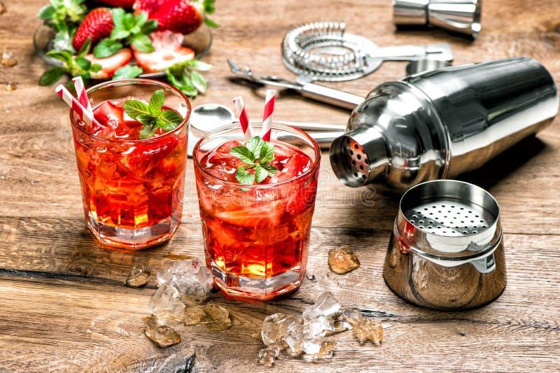 Rotes Getränk mit Eis Cocktail, das Barwerkzeuge herstellt stockfotos