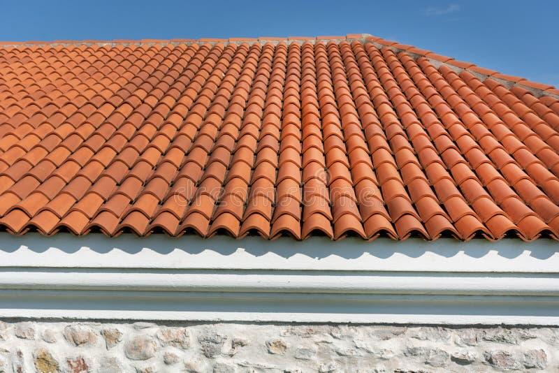 Rotes gewölbtes Fliesenelement des Dachplattemusters auf Haus in blauem und bewölktem Frühlingshimmeltag lizenzfreie stockfotografie