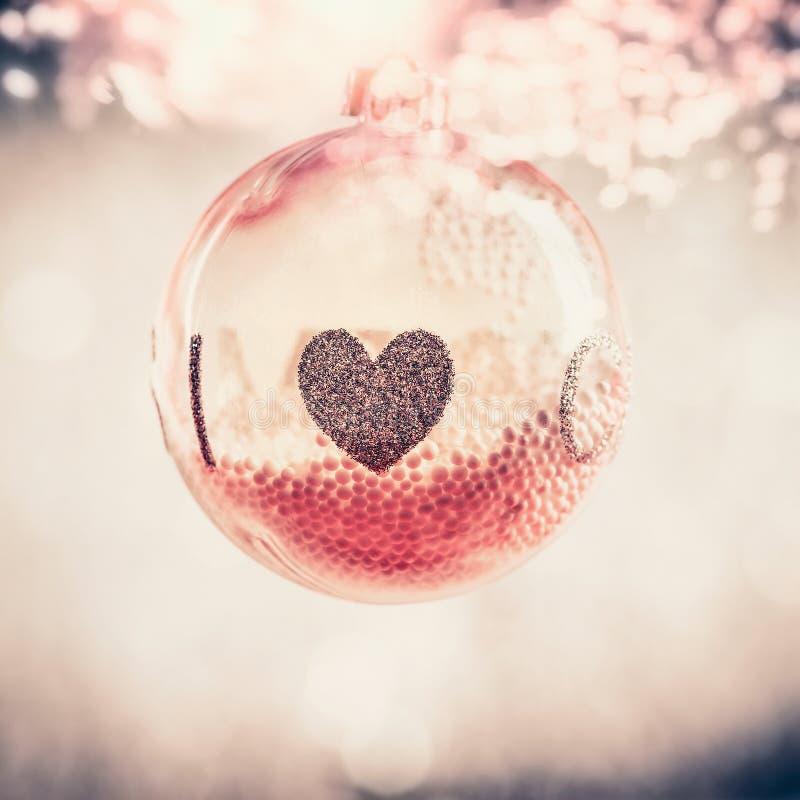 Rotes Glasweihnachtshängender Ball mit Herzen an bokeh Hintergrund lizenzfreies stockbild