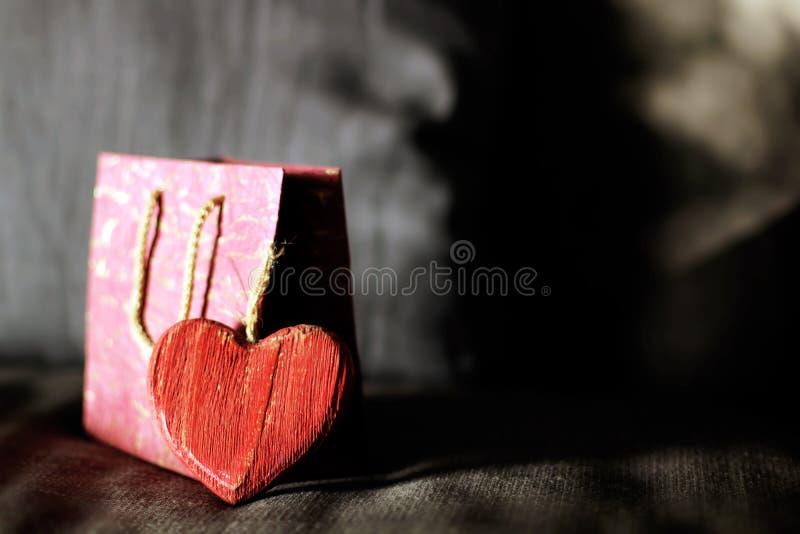 Rotes hölzernes Herz und eine rosa Geschenkbox lizenzfreie stockfotos