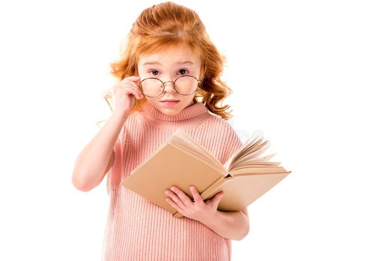 rotes Haarkind, das über Gläsern schaut und Buch hält lizenzfreie stockbilder