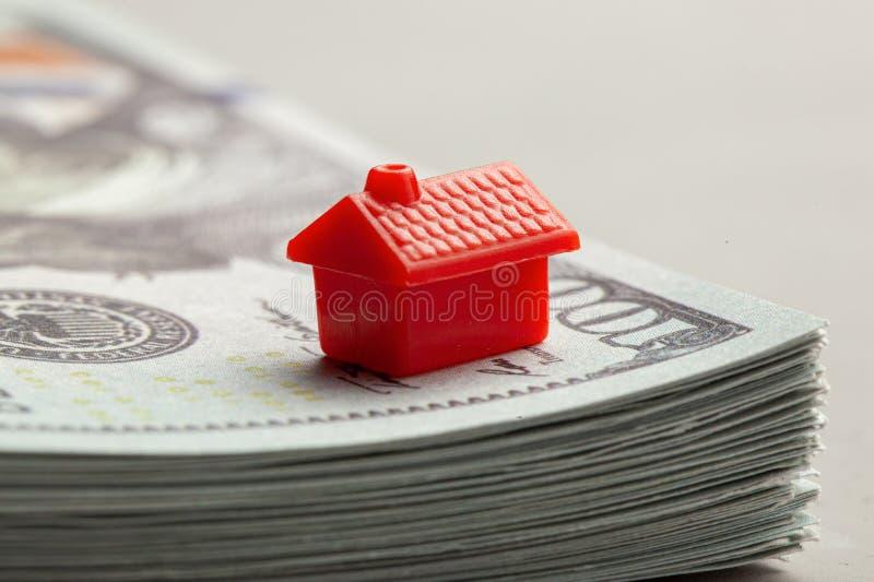 Rotes Haus auf einem Stapel Geld Das Konzept von Steuern oder von Realkrediten stockfotos